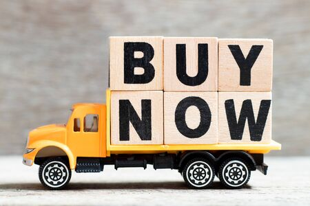 Truck hold letter block in word buy now on wood background