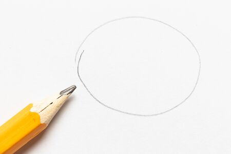 Wooden pencil with round shape drawing on white paper background