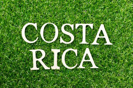 Wood alphabet letter in word costa ricaon green grass background Фото со стока