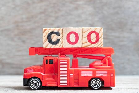 Red fire truck hold letter block in word COO (abbreviation Chief operating officer) on wood background