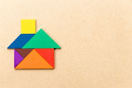 Color tangram puzzle in house or home shape on wood background Reklamní fotografie