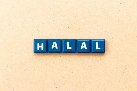 Tile letter in word halal on wood background