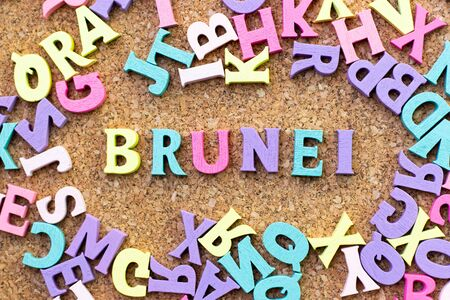 Color alphabet in word Brunei with another letter as frame on cork board background