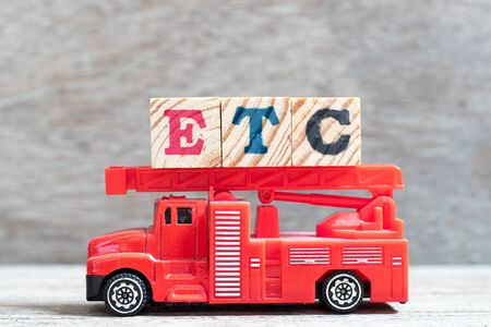 Red fire truck hold letter block in word etc (abbreviation of et cetera) on wood background