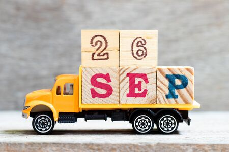 Truck hold letter block in word 26sep on wood background (Concept for date 26 month september) Stock Photo - 130134938