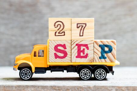 Truck hold letter block in word 27sep on wood background (Concept for date 27 month september)