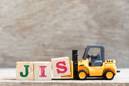 Toy forklift hold letter block s in word JIS (abbreviation of Just in sequence) on wood background