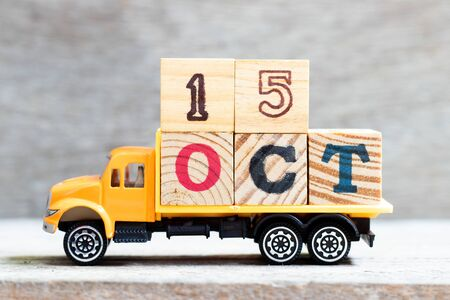 Truck hold letter block in word oct on wood background (Concept for date 15 month October)