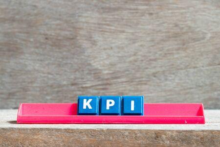 Tile letter on red rack in word KPI (Abbreviation of key performance indicator) on wood background Stok Fotoğraf