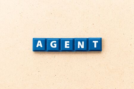 Tile letter in word agent on wood background