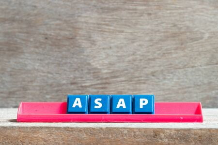 Tile letter on red rack in word ASAP (Abbreviation of as soon as possible) on wood background