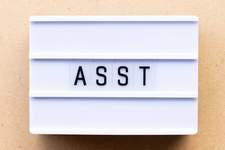 Lightbox with word asst (abbreviation of assistant) on wood background