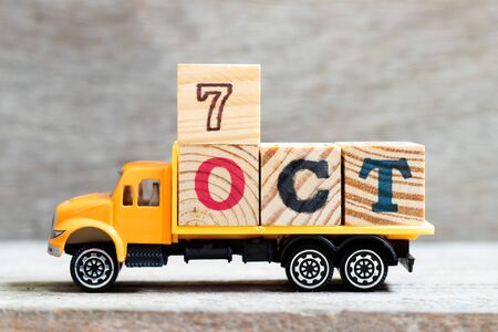Truck hold letter block in word 7oct on wood background (Concept for date 7 month October)