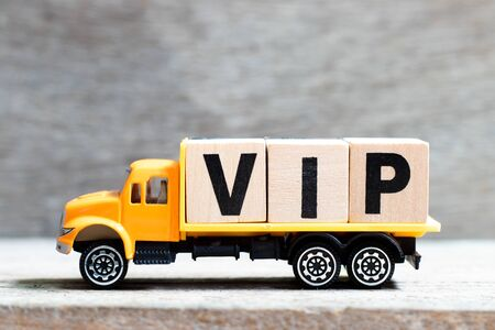 Truck hold letter block in word VIP (abbreviation of very important person) on wood background