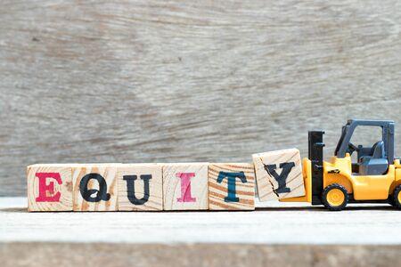 Toy forklift hold letter block y to complete word equity on wood background Reklamní fotografie