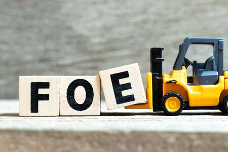 Toy forklift hold letter block e  to complete word foe on wood background