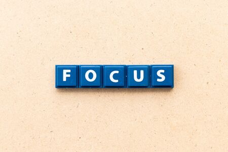 Tile letter in word focus on wood background