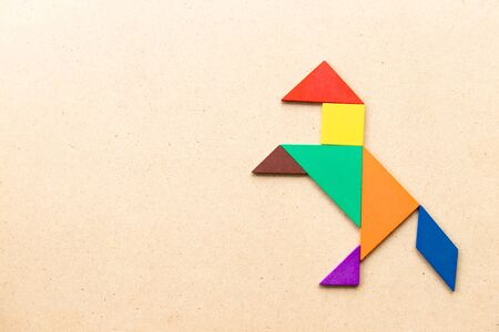 Color tangram puzzle in horse or mustang shape on wood background