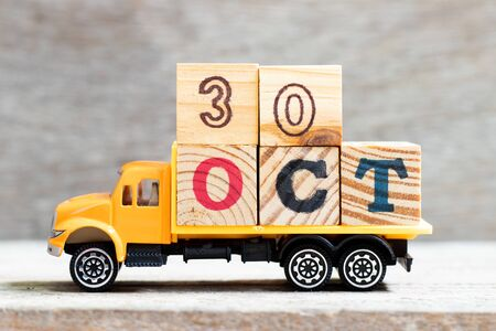 Truck hold letter block in word 30oct on wood background (Concept for date 30 month October)