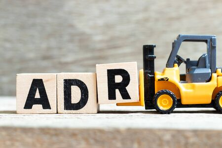 Toy forklift hold letter block r to complete word ADR (Abbreviation of Adverse drug reaction) on wood background