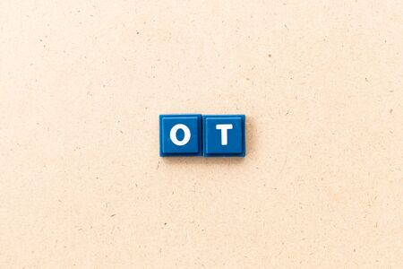 Tile letter in word ot (abbreviation for overtime) on wood background