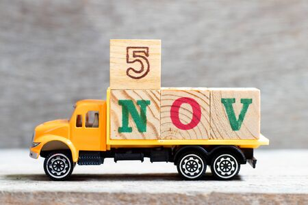 Truck hold letter block in word 5nov on wood background (Concept for date 5 month November)