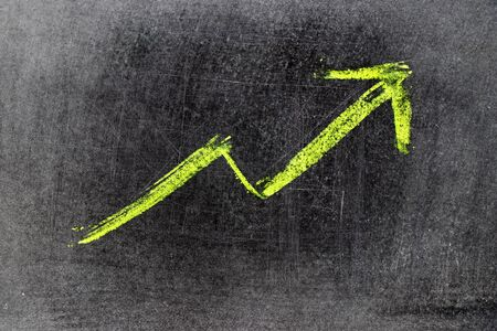 Green chalk draw as upward arrow graph on black board background (Concept for sale, profit, cost of company in uptrend)