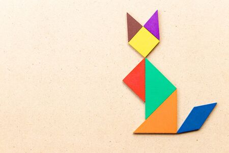Color tangram puzzle in sitting cat shape on wood background