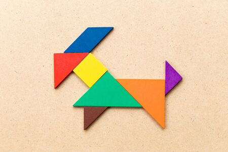 Color tangram puzzle in goat shape on wood background Stock fotó