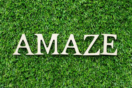 Wood alphabet letter in word amaze on green grass background Фото со стока