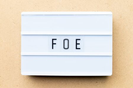 White lightbox with word foe on wood background