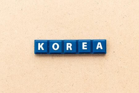 Tile letter in word Korea on wood background