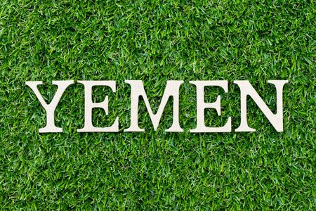 Wood alphabet letter in word Yemen on green grass background