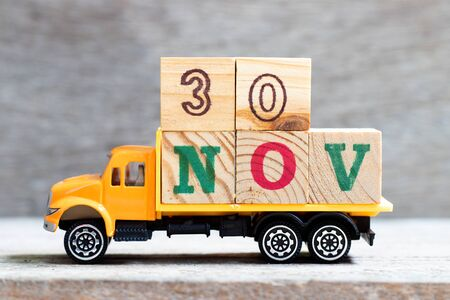 Truck hold letter block in word 30nov on wood background (Concept for date 30 month November)