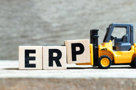 Toy forklift hold letter block p to complete word ERP (Abbreviation of Enterprise Resource Planning) on wood background