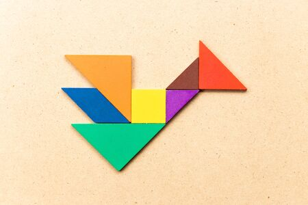 Color tangram puzzle in bird or dragon shape on wood background