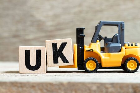 Toy forklift hold letter block k to complete word UK (abbreviation of united kingdom) on wood background