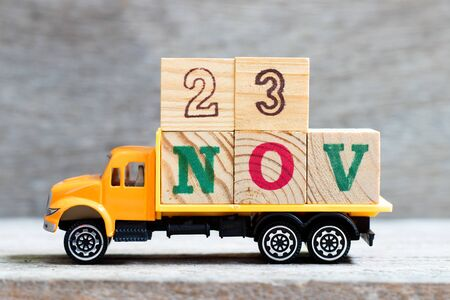 Truck hold letter block in word 23nov on wood background (Concept for date 23 month November)