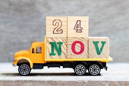 Truck hold letter block in word 24nov on wood background (Concept for date 24 month November)