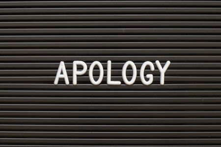 Black color felt letter board with white alphabet in word apology background Фото со стока