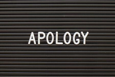 Schwarze Farbe Filz Briefbrett mit weißem Alphabet im Wort Entschuldigung Hintergrund Standard-Bild