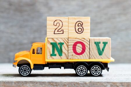 Truck hold letter block in word 26nov on wood background (Concept for date 26 month November) 스톡 콘텐츠
