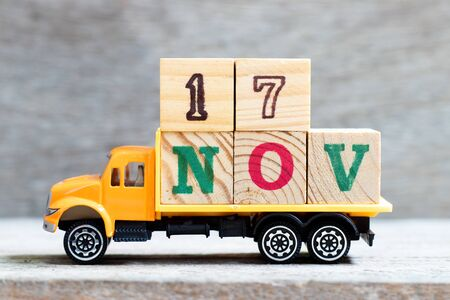Truck hold letter block in word 17nov on wood background (Concept for date 17 month November)
