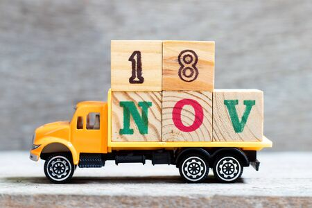 Truck hold letter block in word 18nov on wood background (Concept for date 18 month November) 写真素材