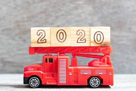 Red fire truck hold letter block in word 2020 on wood background Stock Photo