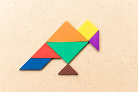 Color tangram puzzle in vulture bird shape on wood background