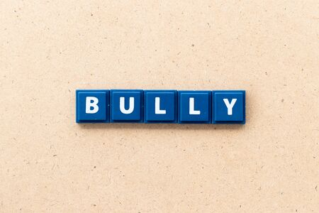 Tile letter in word bully on wood background