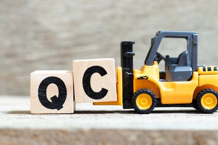 Toy forklift hold letter block c to complete word QC (Abbreviation of Quality Control) on wood background Stok Fotoğraf