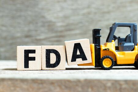 Toy forklift hold letter block A to complete word FDA (abbreviation of food and drug administration) on wood background