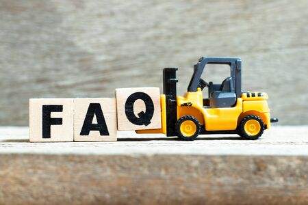 Toy forklift hold letter block q to complete word FAQ (Abbreviation of Frequently Asked Questions) on wood background Stockfoto